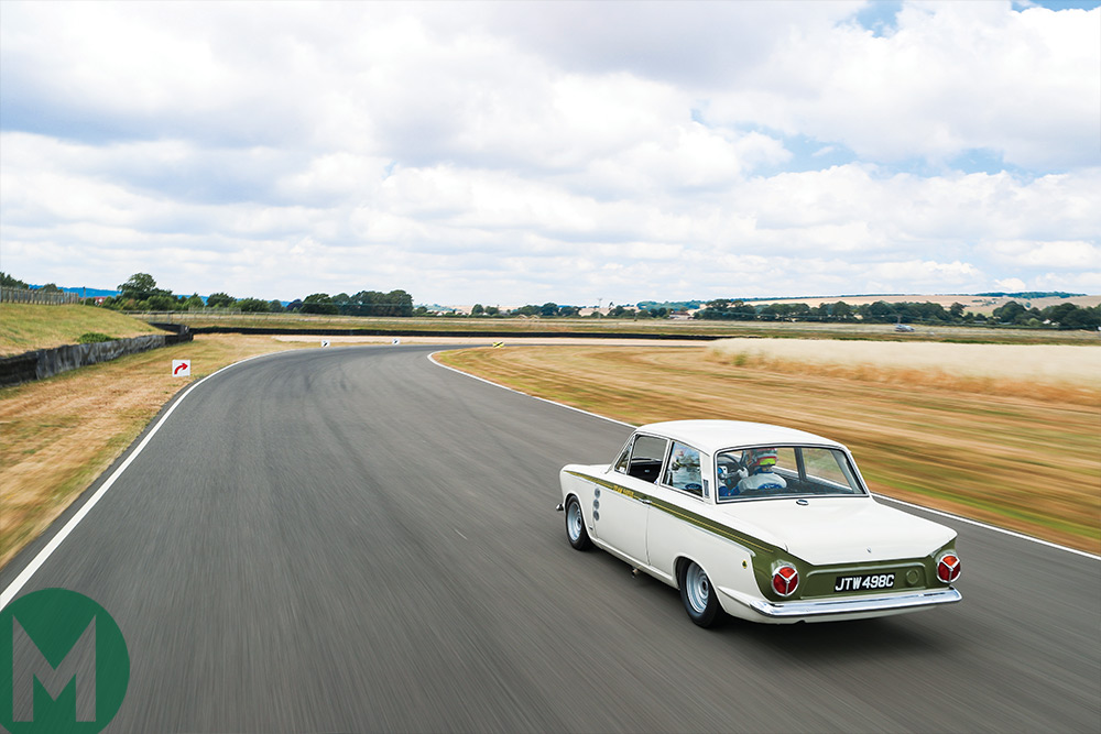 A tracking shot of the Lotus Cortina at Goodwood race circuit